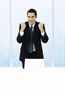 Businessman standing with fists up, smiling at camera