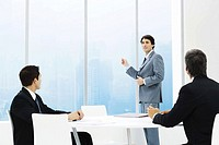 Businessmen in meeting, one standing, pointing out window
