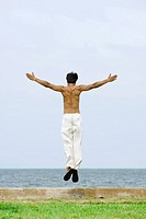 Man jumping in the air at the beach, arms outstretched, rear view