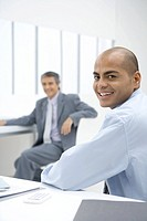 Two businessmen sitting in office, smiling at camera