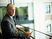 Mature businessman on balcony in office building,holding mobile phone,portrait