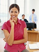 Businesswoman sitting on desk, smiling