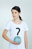 Girl wearing tee-shirt printed with question mark, holding globe, looking away