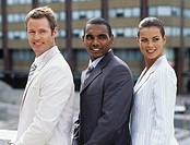 Three business people standing in row outdoors,side view