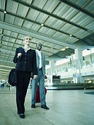 Businessman and woman walking with luggage in airport, low angle view