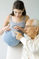 Grandfather and granddaughter looking at globe together