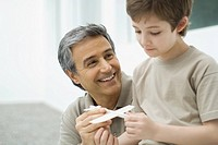 Mature man and boy holding toy plane