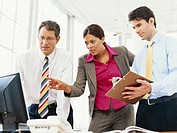 Businessmen and businesswoman using computer, low angle view
