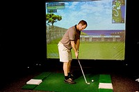 Man playing virtual golf