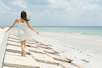 Young woman walking along low wall at the beach, rear view