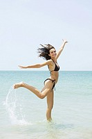 Young woman at the beach jumping, one leg up, arms raised