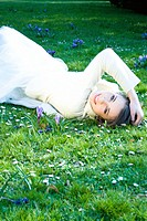 Teenage girl lying on the ground with hand on head, smiling at camera