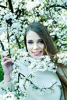 Teenage girl standing among flowering tree, smiling at camera, portrait (thumbnail)