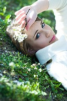 Teenage girl lying on the ground, holding flowers, smiling at camera