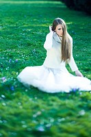Teenage girl sitting in grass, hair partially covering face, looking away