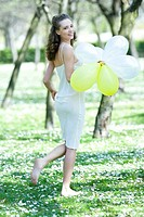 Young woman walking barefoot in meadow, holding balloons, smiling over shoulder at camera