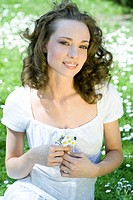 Young woman sitting outdoors, holding flowers, smiling at camera, portrait