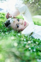 Teenage girl lying in grass, holding flowers against head, looking at camera
