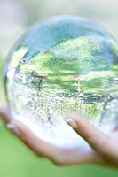 Woman holding glass ball in hand outdoors, extreme close-up
