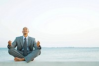 Businessman sitting in lotus position at the beach, eyes closed