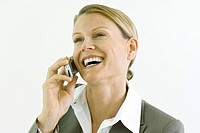 Businesswoman using cell phone, smiling, looking away
