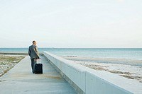 Businessman walking on sidewalk at the beach, pulling suitcase behind him, looking at view