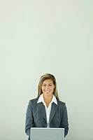 Businesswoman using laptop computer, smiling at camera (thumbnail)