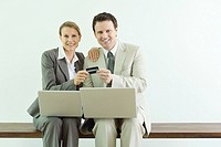 Man and woman sitting, holding credit card together, both dressed in suits with laptop computers