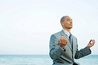 Businessman sitting by the sea in lotus position, eyes closed