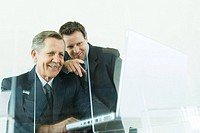 Two businessmen looking at laptop computer together, both smiling, low angle view