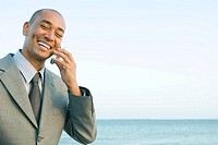 Businessman at the beach using cell phone, smiling, eyes closed