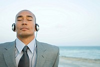 Businessman listening to headphones at the beach, eyes closed, close-up