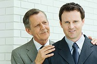 Businessman with hands on younger associate's shoulders, associate smiling at camera