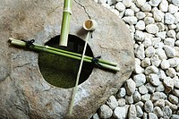 Stone basin with bamboo ladle and gravel, high angle view