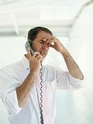 Businessman using phone,upper half,hand on head