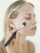 Beautician applying blush on young woman´s cheek