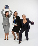 Group portrait of three business women with skittles ball and award