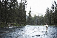 Young woman fly-fishing in river