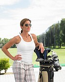 Woman leaning on golf bag, standing on drive range