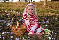 girl with Easter basket in spring meadow