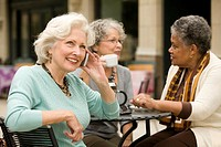 Three senior women sitting at cafe table, one talking on mobile phone