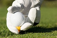 A person placing a golf ball on a tee