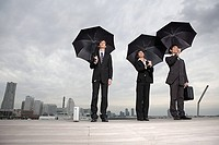 Businesspeople holding umbrellas
