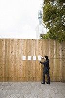A businessman attaching paper to a fence