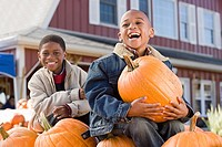 Portrait of boys sat on pumpkins