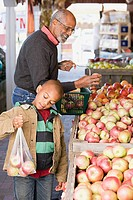 A boy and his grandfather choosing apples