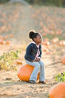 A girl sat on a pumpkin
