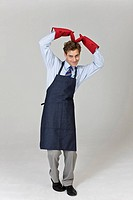 Man wearing suit with apron, cooking gloves