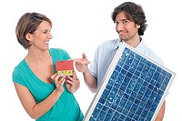 Couple holding house and solar panel