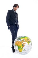 Businessman standing by globe